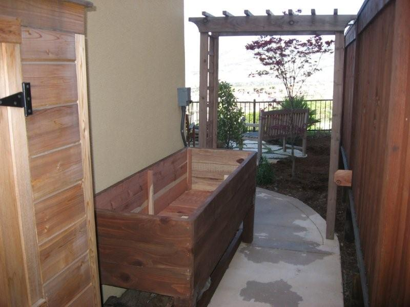 A completed DIY vegetable planter box at side of home
